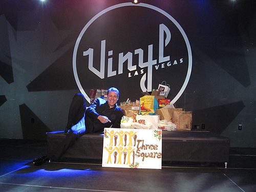 Headliner Mark OToole strikes a pose with donations for Three Square Food Bank